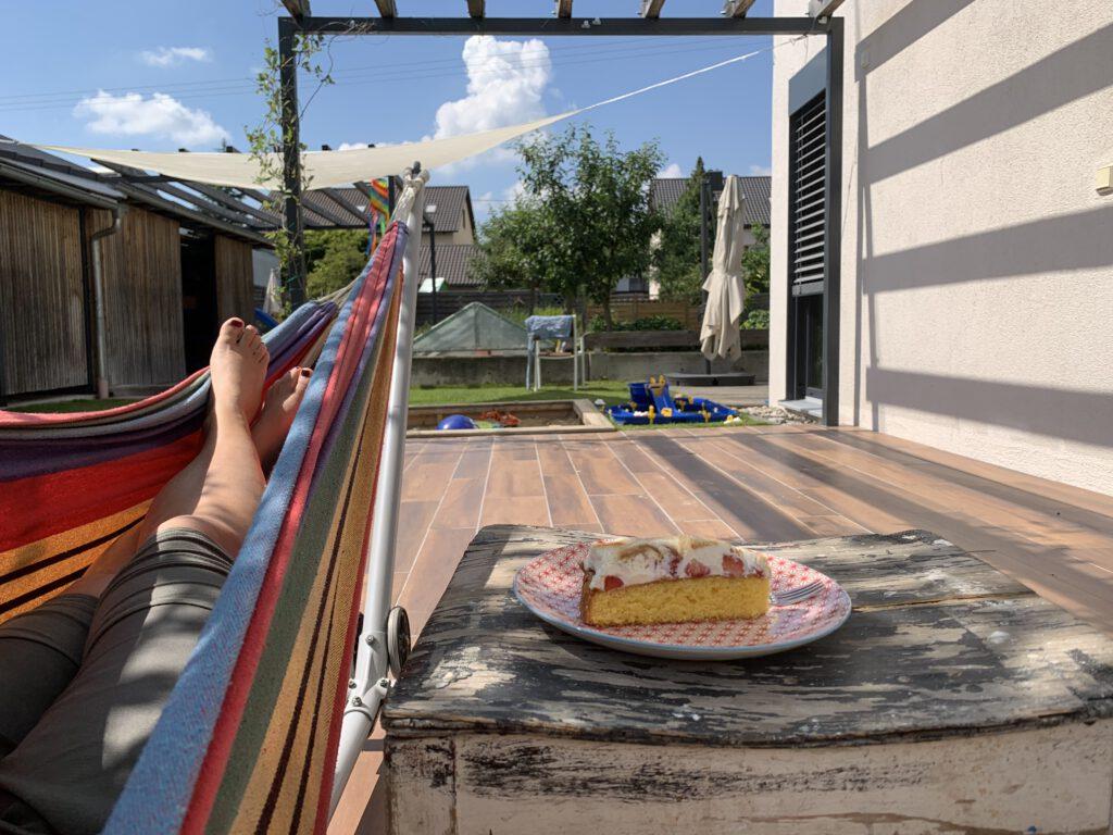 Foto von Hängematte, Kuchen daneben, Sandkasten und Wäscheständer sind zu erkennen.